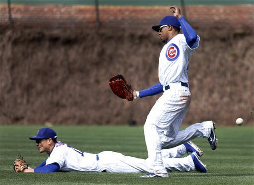 Chicago Cubs right fielder Julio Borbon, right, is unable to catch a shallow pop fly off the bat of San Diego Padres' Yonder Alonso, scoring Jesus Guzman, as second baseman Darwin Barney falls to the turf during the eighth inning of a baseball game Thursday, May 2, 2013, in Chicago. (AP Photo/Charles Rex Arbogast)