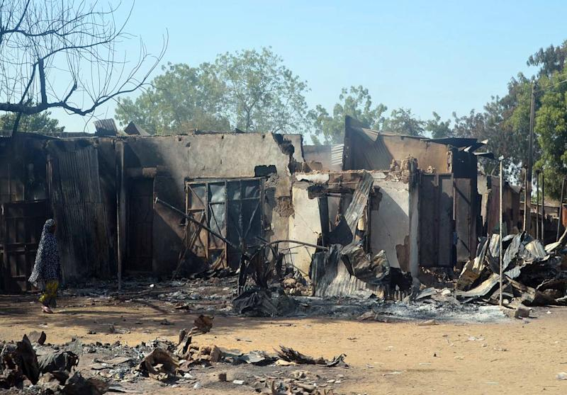 A woman walks past burnt houses after an attack by Boko Haram Islamists on February 20, 2014 in the northeast Nigerian town of Bama (AFP Photo/)