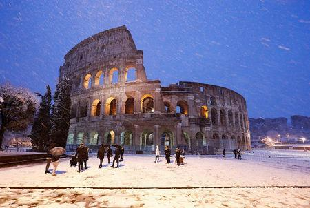 The ancient Colosseum is seen during a heavy snowfall early in the morning in Rome. REUTERS/Remo Casilli
