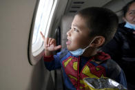 Yancarlos Amaya, 5, a migrant from Honduras, looks out an airplane window in Harlingen, Texas, as he and his mother, Celestina Ramirez, ride on an airplane to Houston, Wednesday, March 24, 2021. The mother and son, who were headed to Baltimore to reunite with Ramirez's brother, were permitted to stay in the U.S. after turning themselves into U.S. Customs and Border Protection upon crossing the border. (AP Photo/Julio Cortez)