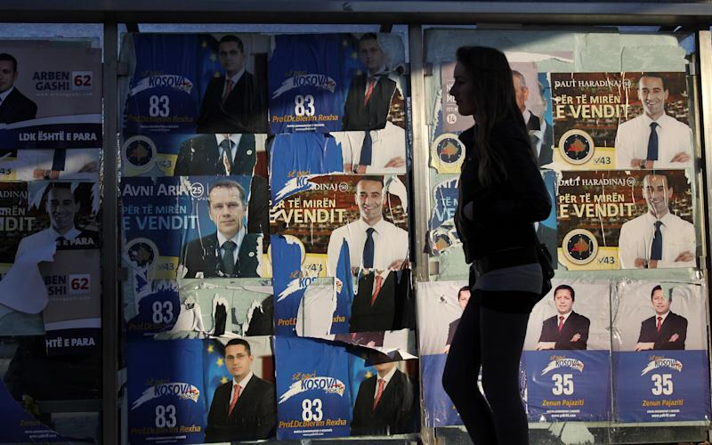 CORRECTS DATE TO SATURDAY DEC. 11, 2010  - A Kosovo woman walks past electoral posters in a bus station in Kosovo's capital Pristina on Saturday, Dec. 11, 2010. Political parties in Kosovo wrapped up a 10-day election campaign before this weekend's ballot, the first general poll since the country's declaration of independence from Serbia in 2008 and amid fears the new country faces a partition along ethnic lines.   (AP Photo/Visar Kryeziu)
