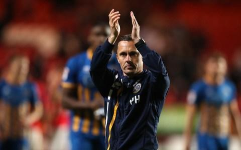 "For Paul Hurst, the ambitious Shrewsbury Town manager, Sunday afternoon's League One play-off final is the football equivalent of a Casablanca moment: of all the teams in all the world, he had to be drawn against Rotherham. This was the club where he spent the entirety of his playing career, turning out in the red and white shirt for 15 seasons between 1993 and 2008, a defensive stalwart as the club gained promotion from League Two, then League One before spending four seasons in the Championship. Now he is playing them for the chance to gain elevation to football's second tier. ""I don't know if it was because I wasn't very good and couldn't secure a move anywhere else,"" he says of his one-club record, his accent giving hint of his Yorkshire origins. ""A lot of people have said it's fate that we're playing them. All I know is, once the game starts, my allegiance is clearly with Shrewsbury."" As if the challenge was not already substantial enough, the identity of the manager in the opposition technical area makes this the most personal of encounters for Hurst: he played directly behind Paul Warne for Rotherham more than 200 times across six seasons. Not that he expects any cordiality once the whistle blows. ""One thing I know about Warnie, he's hugely competitive,"" says Hurst. ""But then so am I. Sometimes that came between us. I can remember one training session, he booted me and I booted him straight back. For that ten minutes we didn't like each other. It was soon forgotten, but I wouldn't be surprised if we have a few words [during the game]."" Paul Hurst (left) in action for Rotherham against Arsenal in 2003 Credit: GETTY MAGES Meeting up with his old mate and his old club in such an auspicious match was not something Hurst ever imagined happening. Not least because, when the season began, rather than candidates for promotion to the Championship Shrewsbury were universally reckoned favourites for relegation. So much so, that, as a motivational spur, the manager pinned to the dressing room wall a league table published by a bookmaker which predicted that the club was destined for the drop. ""Oh, we've massively surprised ourselves,"" he says. ""Having managed to stay in the league last year, I was optimistic we could survive a little more comfortably this season. But this is all a little surreal; to be in with a shout for automatic promotion for so long was an amazing achievement in itself."" Amazing because, ever since Hurst took over in December 2016, he has been working with one of the smallest budgets in League One. So modest are finances in this part of Shropshire that, when he tried to sign a player last summer, he was unable to match the terms being offered by Lincoln City, then freshly promoted from the National League. ""When I was at Rotherham, the lads who used to play cards on the bus would say that realistically those with the most money won, because they could keep going and going till everyone else bottled out. I'm trying to prove them wrong, show it's not all about money."" Paul Hurst celebrating with his players after they reached the play-off final Credit: getty images Instead of cash, as his team have sought promotion, Hurst says he has relied on two things: science and spirit. The science comes from relentlessly tracking how far each of his players runs in a game, setting targets then subtly increasing them once they have been reached. ""When we hit a certain number, more often than not we won. We certainly didn't lose,"" he says. ""People might say every team works hard. Trust me, some work harder than others."" And, according to the club's Congolese international centre back Aristote Nsiala, the spirit has been generated among the club's small, tight-knit first team squad by the manager's approach. ""His man management is on a different level,"" says Nsiala. ""He just lets you play. Yeah, we do go through formations, watch videos, do our homework. But he makes it clear he believes in his players and lets you get on with it. Every day you come in he's always got a smile on his face."" Which, Hurst suggests, is not entirely accidental. ""If you enjoy going into work, you'll work harder, whatever you do for a living,"" he says. ''And we work hard."" It is a managerial approach which has been noted: as Shrewsbury have made their way to Wembley, so Hurst's name has increasingly been mentioned in connection with vacancies at more renowned clubs. Paul Hurst has been linked with bigger clubs Credit: pa ""I'm not trying to pretend that I don't realise my stock has risen, I've had far more personal publicity than I ever have had before,"" he says. ""But that is only a by-product of the team and club doing well. I hope I am a part of that, allowing people to do their jobs. But I am only a part. From my point of view it's nice people are talking, it proves we are doing something right."" Though as he approaches by far the most important game of his managerial career, he accepts that all of the attributes which have taken Shrewsbury this far are likely to be matched by their opponents. ""We are very similar,"" he says of sides who beat each other 1-0 during the league season. ""Two very fit teams, working very hard. Paul and I are not afraid as managers to highlight work rate as one of our strengths."" It is, he adds, something that both learned from their time together on the pitch. ""The team Paul and I had most success with at Rotherham, I don't think I'll hurt anybody's feelings by saying this, we weren't the most talented group. But we gave 100 per cent. Nobody enjoyed playing us. Paul ran and ran and ran. He was so fit, he could probably do that now."" Though he hopes at Wembley that Warne will be running away empty-handed."