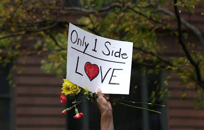 """A demonstrator holds a banner reading """"Only 1Side Love"""" during a protest at Federal Plaza Square in Chicago on Aug. 13."""