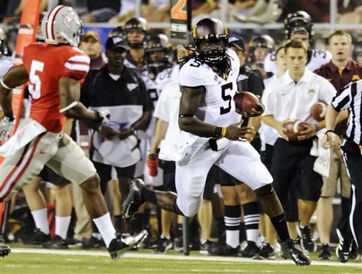 Minnesota quarterback MarQueis Gray (5) looks to run past UNLV's Dre Crawford (5) during the first half of an NCAA college football game, Thursday, Aug. 30, 2012, in Las Vegas. (AP Photo/David Becker)