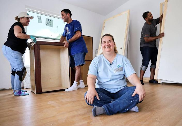 Maribel Gonzalez, 41, sits on the newly installed floor of her new Habitat for Humanity of Greater Miami home in South Miami-Dade's Goulds neighborhood while volunteers Vivian Marazzi, left, Alex Navarro and Keir Rocha, right, bring in newly delivered doors and cabinets. Gonzalez and seven other new soon-to-be homeowners are helping hammer together their houses during Habitat's annual Blitz Build. The nonprofit recently marked 30 years in operation.