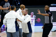 Michigan head coach Juwan Howard is restrained after being ejected from the game in the second half of an NCAA college basketball game against Maryland at the Big Ten Conference tournament in Indianapolis, Friday, March 12, 2021. (AP Photo/Michael Conroy)
