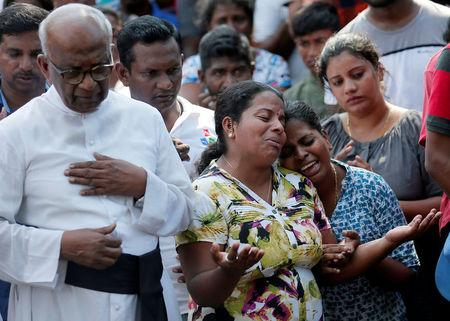 FILE PHOTO:  People react during a mass burial of victims, two days after a string of suicide bomb attacks on churches and luxury hotels across the island on Easter Sunday, in Colombo