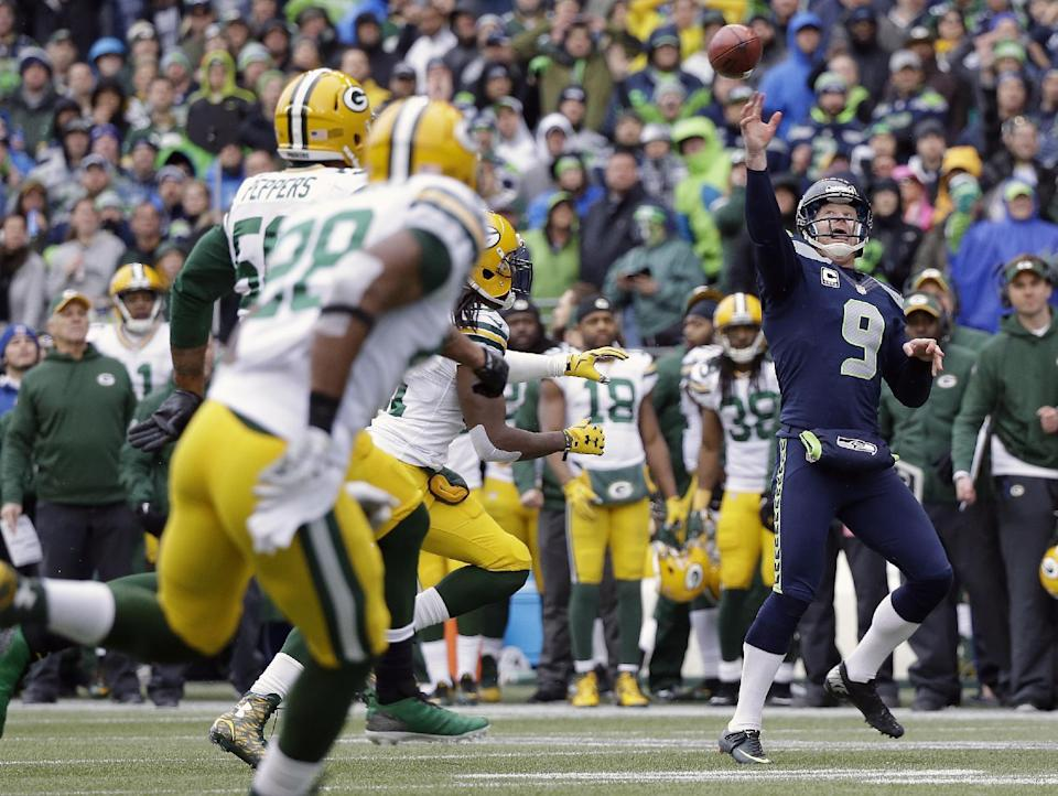 Seattle Seahawks' Jon Ryan (9) throws a touchdown pass on a fake field goal attempt during the second half of the NFL football NFC Championship game against the Green Bay Packers Sunday, Jan. 18, 2015, in Seattle. (AP Photo/Jeff Chiu)