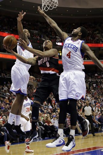 Portland Trail Blazers' Damian Lillard (0) shoots between Philadelphia 76ers' Charles Jenkins, left, and Dorell Wright during the first half of an NBA basketball game, Monday, March 18, 2013, in Philadelphia. (AP Photo/Matt Slocum)