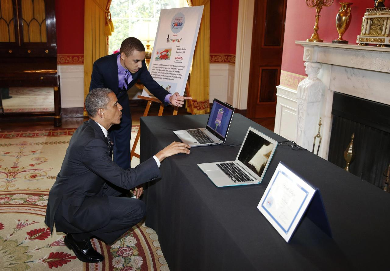 U.S. President Barack Obama listens to Nicolas Badila, of Jonesboro, Georgia, as he hosts the 2014 White House Science Fair in the Red Room at the White House in Washington, May 27, 2014. REUTERS/Larry Downing (UNITED STATES - Tags: POLITICS SCIENCE TECHNOLOGY)
