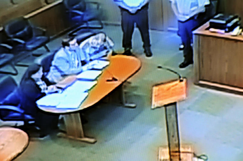 In this photo from a video monitor at the Union County Courthouse in Jonesboro, Ill., Anthony Garcia, in striped shirt, an Indiana doctor who is a suspect in four killings in Nebraska, looks down at paperwork while seated with his attorneys, Alison and Bob Motta, during his extradition hearing on Wednesday, July 17, 2013. Garcia waived extradition and will return to Omaha to face murder charges. Garcia, who lives in Terre Haute, Ind., was arrested Monday in Union County in southern Illinois. (AP Photo/The Southern, Paul Newton)