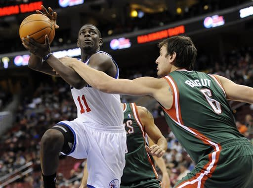Philadelphia 76ers' Jrue Holiday (11) drives past Milwaukee Bucks' Andrew Bout (6), of Australia, in the first half of and NBA basketball game on Monday, Jan. 16, 2012, in Philadelphia. (AP Photo/Michael Perez)