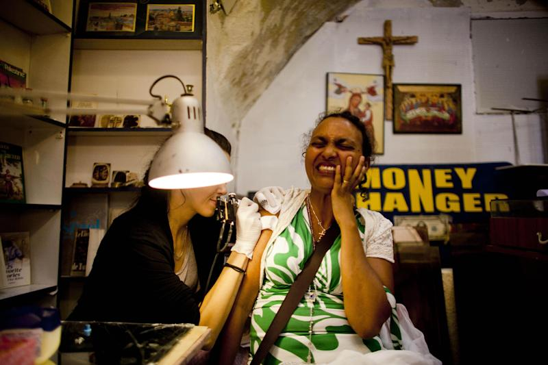 In this Saturday, May 10, 2013 photo, Etetu Legesse, a Christian Orthodox pilgrim from Ethiopia, reacts as she receives a tattoo in a shop owned by the Razzouk family in Jerusalem. The Razzouk family has been tattooing pilgrims with crosses and other religious symbols for hundreds of years, testament to the importance of the ancient ritual. While Catholics can get a written certificate of their pilgrimage to Jerusalem, Orthodox Christians opt for a tattoo, a permanent reminder of their visit. (AP Photo/Dusan Vranic)