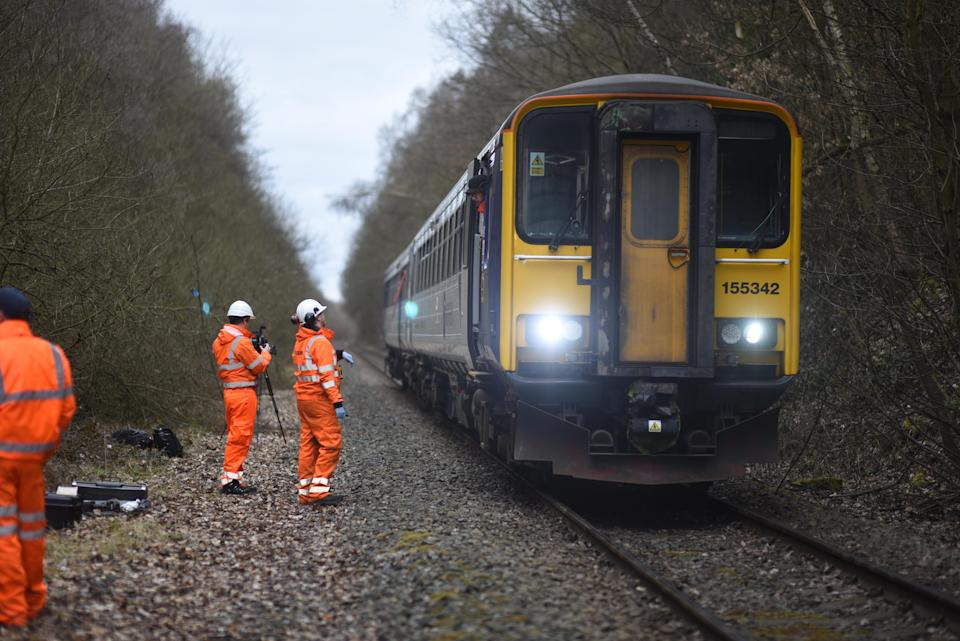 Engineers stand next to a Northern train