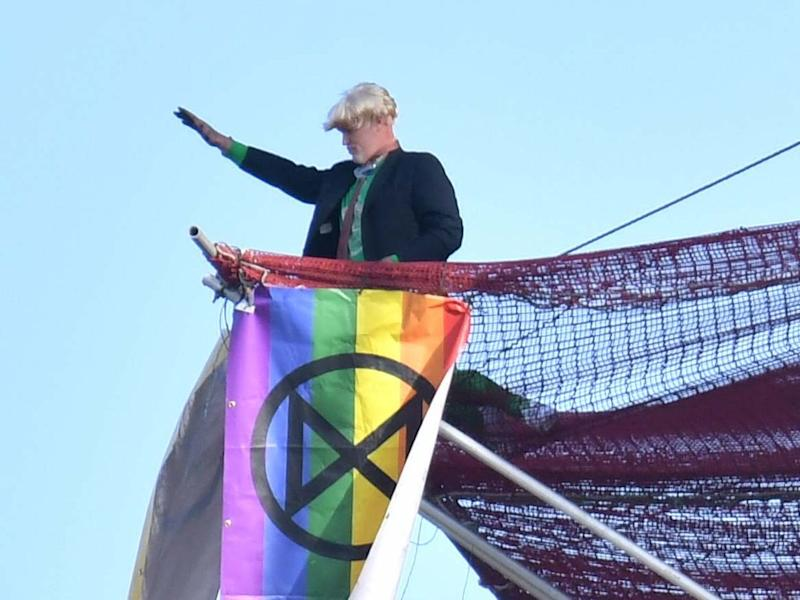 An Extinction Rebellion protester who scaled the scaffolding surrounding Big Ben unfurls a banner: Dominic Lipinski/PA