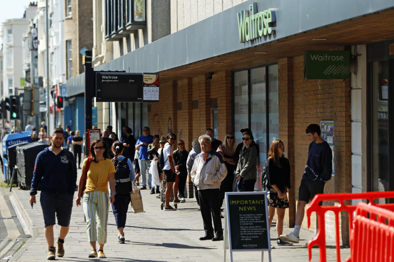 A long queue of people wait outside of Waitrose in Brighton as the UK continues in lockdown to help curb the spread of the coronavirus.