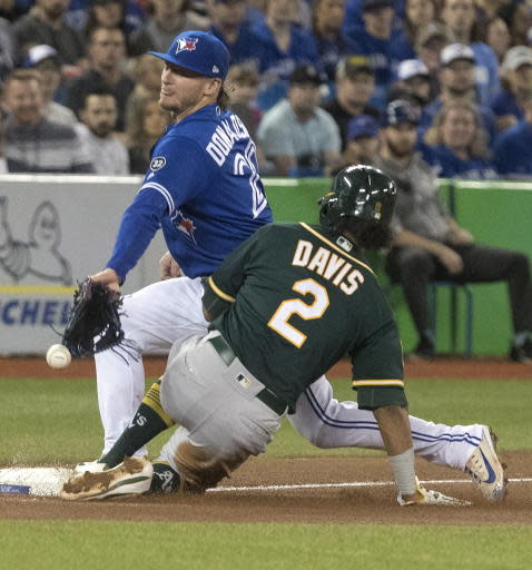 Oakland Athletics' Khris Davis slides safely into third as Toronto Blue Jays third baseman Josh Donaldson tries to make a play in the eighth inning of a baseball game in Toronto, Saturday, May 19, 2018. (Fred Thornhill/The Canadian Press via AP)