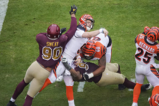 Cincinnati Bengals quarterback Joe Burrow (9) is hit and sandwiched inbetween Washington Football Team defensive end Montez Sweat (90), defensive tackle Jonathan Allen (93) and Cincinnati Bengals offensive guard Mike Jordan (60), during the second half of an NFL football game, Sunday, Nov. 22, 2020, in Landover, Md. After throwing a pass, Burrows was injured on this play and was carted off the field. (AP Photo/Al Drago)