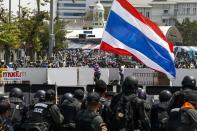 Anti-government protesters gather behind barricades as Thai riot police officers take cover near Government House in Bangkok February 18, 2014. A Thai police officer was killed and dozens of police and anti-government protesters were wounded in gun battles and clashes in Bangkok on Tuesday, officials and witnesses said. REUTERS/Athit Perawongmetha(THAILAND - Tags: POLITICS CIVIL UNREST)