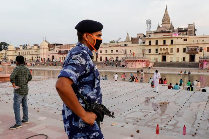 An armed police officer stands guard on the bank of Sarayu river ahead of the foundation-laying ceremony for a Hindu temple in Ayodhya