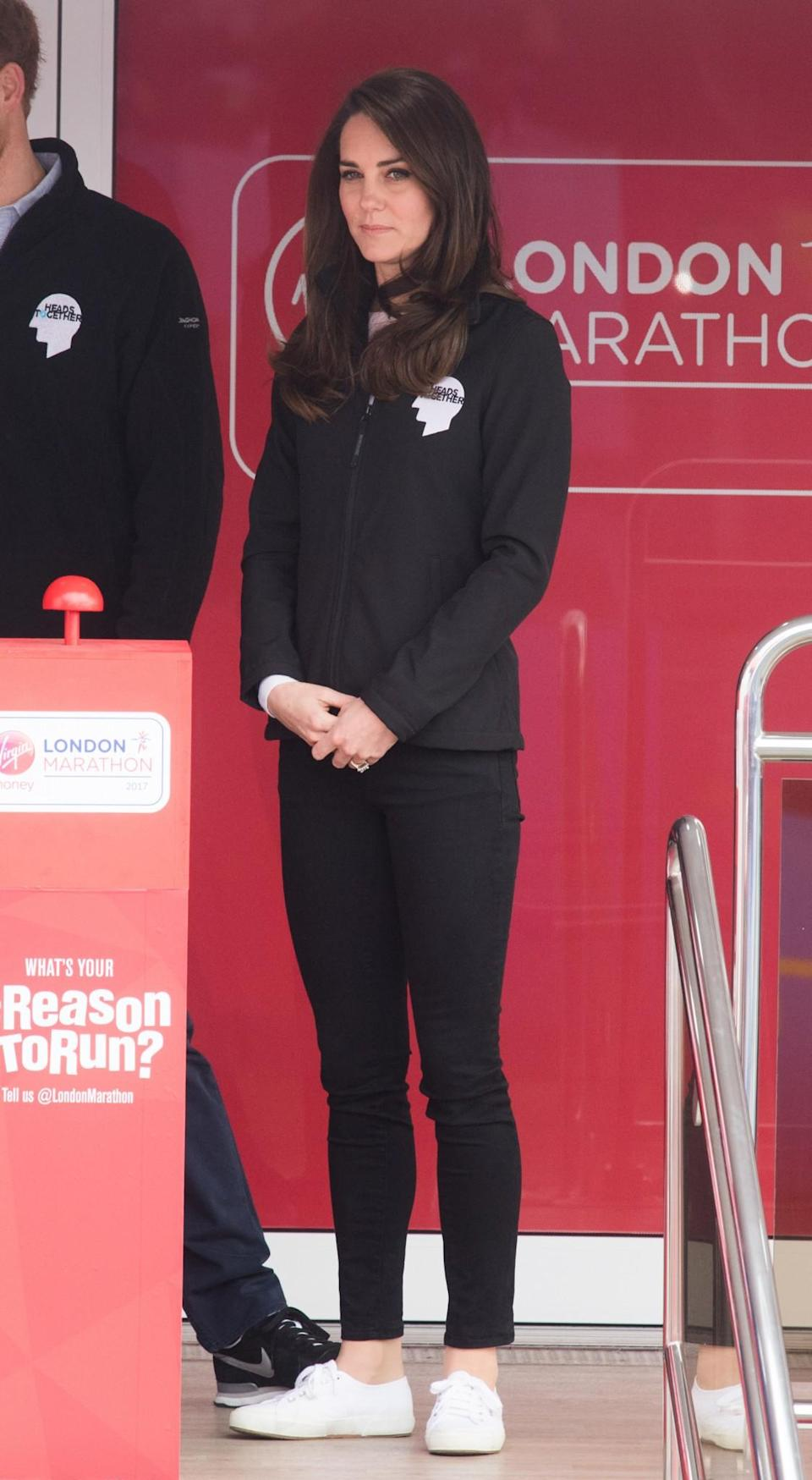 <p>Kate supported runners at the 2017 London Marathon wearing a black jacket branded with the Heads Together logo. (Heads Together is the mental health charity set up by the Duchess and Princes William and Harry.) She paired her off-duty look with skinny black jeans and a white pair of Superga trainers.<br><i>[Photo: PA]</i> </p>