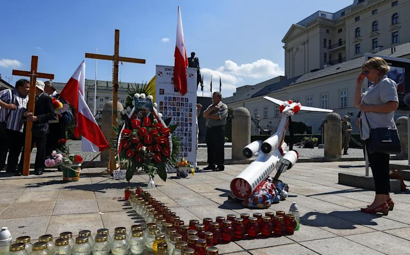 People hold a ceremony honoring President Lech Kaczynski and dozens of officials who were killed two years ago in a plane crash in thick fog near Smolensk, Russia, in Warsaw, June 10, 2012. They hold such commemorations on the 10th of each month because the crash occurred on April 10. Polish authorities were worried that tensions could arise Sunday because the Russian football squad is staying in a hotel next to the spot where the monthly observances take place, ahead of the team's final two Euro 2012 group games in Warsaw. (AP Photo/Sergey Ponomarev)