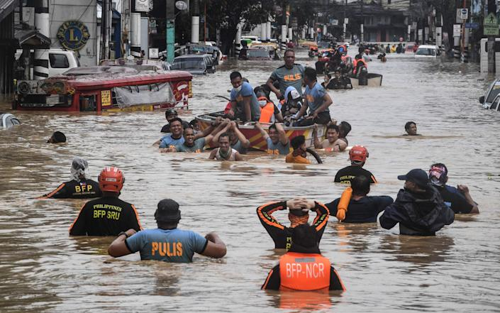 Rescuers pull a rubber boat carrying residents through a flooded street - AFP