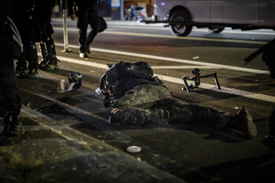 In this Aug. 5, 2020 photo, an activist who was filming protests lies on the street after being tackled by a police officer in Portland, Ore. His camera rig is seen on the ground nearby. Most police officers who violate citizens' rights get away with it because the law is heavily stacked in their favor, legal experts say. (Maranie Rae Staab via AP)