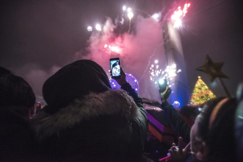 People watch the fireworks during the New Year's Eve celebrations held at Nathan Phillips Square in Toronto