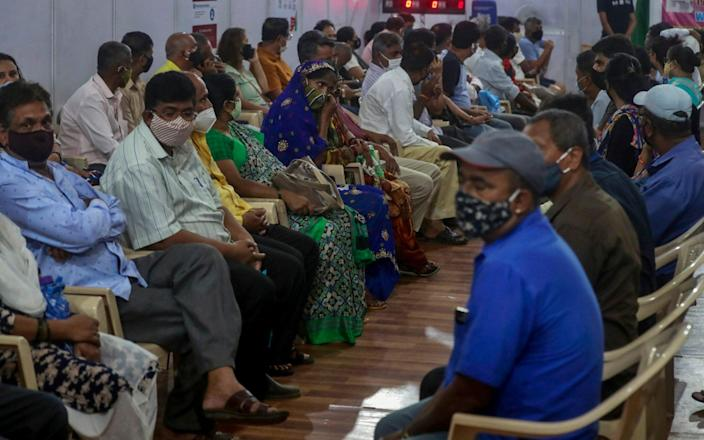 Residents in India wait to receive the vaccine for Covid-19 at a vaccination center in Mumbai - AP