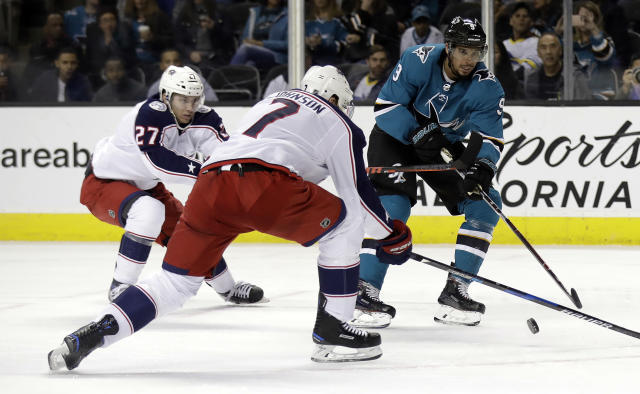 Columbus Blue Jackets' Jack Johnson (7) blocks a shot from San Jose Sharks' Evander Kane, right, during the second period of an NHL hockey game Sunday, March 4, 2018, in San Jose, Calif. (AP Photo/Marcio Jose Sanchez)
