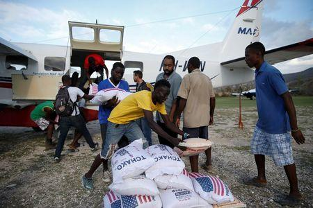 Men carry sacks of rice out from an airplane loaded with food at the airport after Hurricane Matthew passes Jeremie, Haiti, October 7, 2016. REUTERS/Carlos Garcia Rawlins