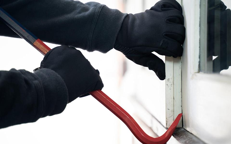 Burglar trying to break into a house with a crowbar - Michael Deacon/GETTY IMAGES