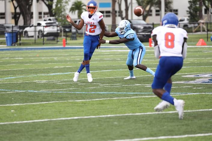 Florida Memorial sophomore quarterback Antoine Williams evades a Keiser defender while attempting to pass to freshman running back George Young.