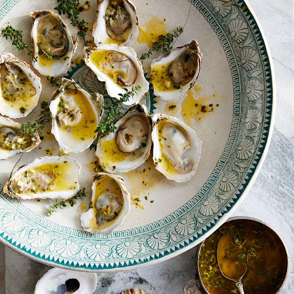 <p>If you've never cooked oysters on the grill, you're in for a treat. Grilling oysters whole saves you the trouble of shucking them--they magically pop open when cooked. A simple garlic herb butter adds richness and a bright pop of flavor to this impressive appetizer. To pretty it up use Irish butter, which is extra-golden because Irish cows typically enjoy an all-grass diet.</p>
