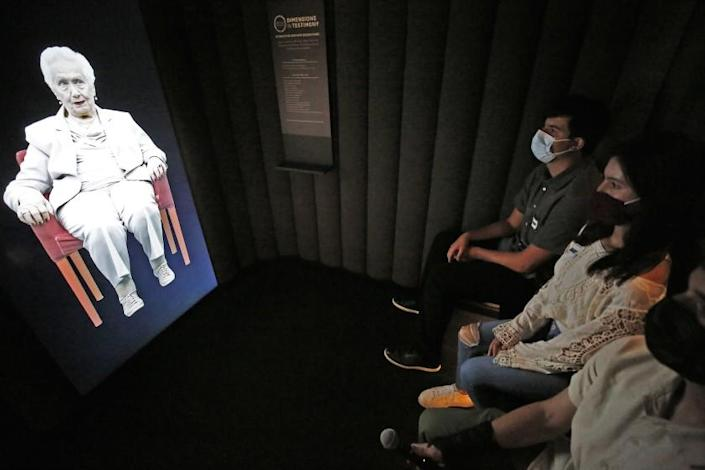 """LOS ANGELES, CA - JULY 29: Students Jacob Manela, Sophia Kangavari and Will Spangler, left to right, interact with 97-year-old Holocaust survivor Renee Firestone -- one of the oldest remaining such survivors in the world appearing in """"Dimensions in Testimony,"""" which gives visitors the opportunity to have a virtual """"one-on-one"""" conversation with Renee as a Holocaust survivor. The pioneering project integrates advanced filming techniques, specialized display technologies and next-generation natural language processing to create an interactive biography so there viewer can receive real-time responses to questions from pre-recorded video images. """"Our museum was founded by survivors who wanted to share their stories publicly and educate the next generation,"""" said Beth Kean, CEO of the Museum. """"With 'Dimensions in Testimony,' countless future generations of visitors and students can hear those stories from the survivors and learn directly from those who were there, even when they are no longer with us."""" Holocaust Museum on Thursday, July 29, 2021 in Los Angeles, CA. (Al Seib / Los Angeles Times)."""