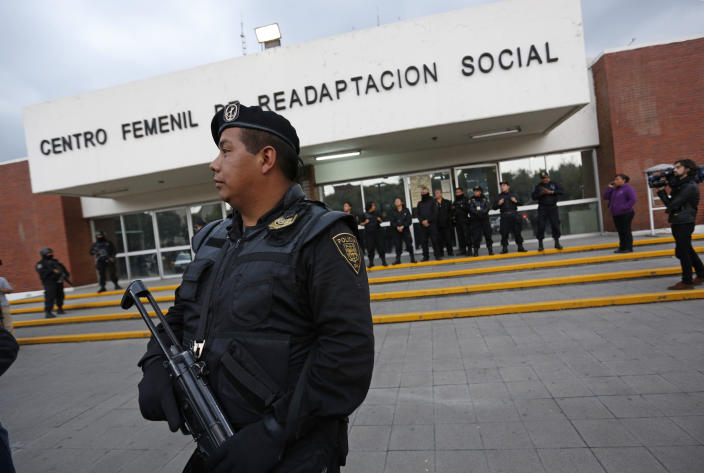 """A police officer stands guard outside a prison where Frenchwoman Florence Cassez had been held in Mexico City, Wednesday, Jan. 23, 2013. A Mexican Supreme Court panel voted Wednesday to release Cassez, a Frenchwoman who says she was unjustly sentenced to 60 years in prison for kidnapping and whose case became a cause celebre in France, straining relations between the two countries. A police convoy with sirens flashing escorted a white sports utility vehicle out of the prison where Cassez had been held later Wednesday, presumably carrying her to the Mexico City airport. Relatives of kidnap victims angrily shouted """"Killer!"""" as the vehicle pulled away. (AP Photo/Andres Leighton)"""