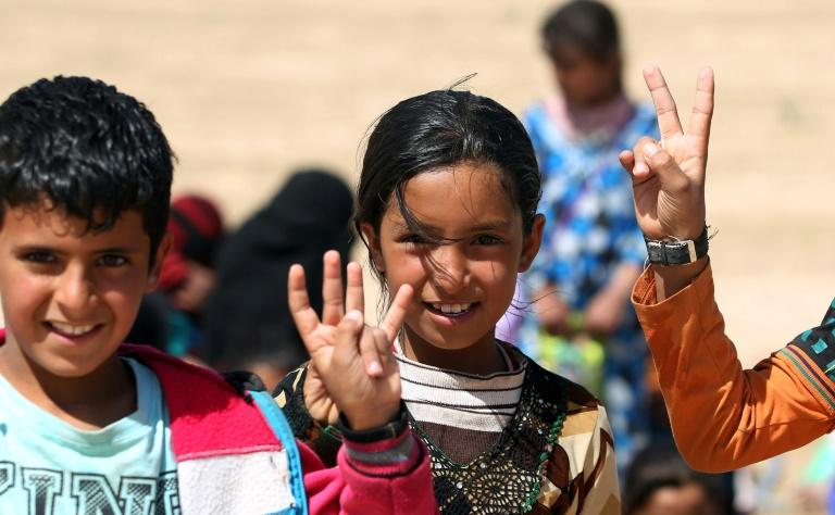 Displaced Iraqi children wave the victory sign during their evacuation from the Hatra area on April 26, 2017, as paramilitary forces pressed an offensive to retake the town from Islamic State group fighters