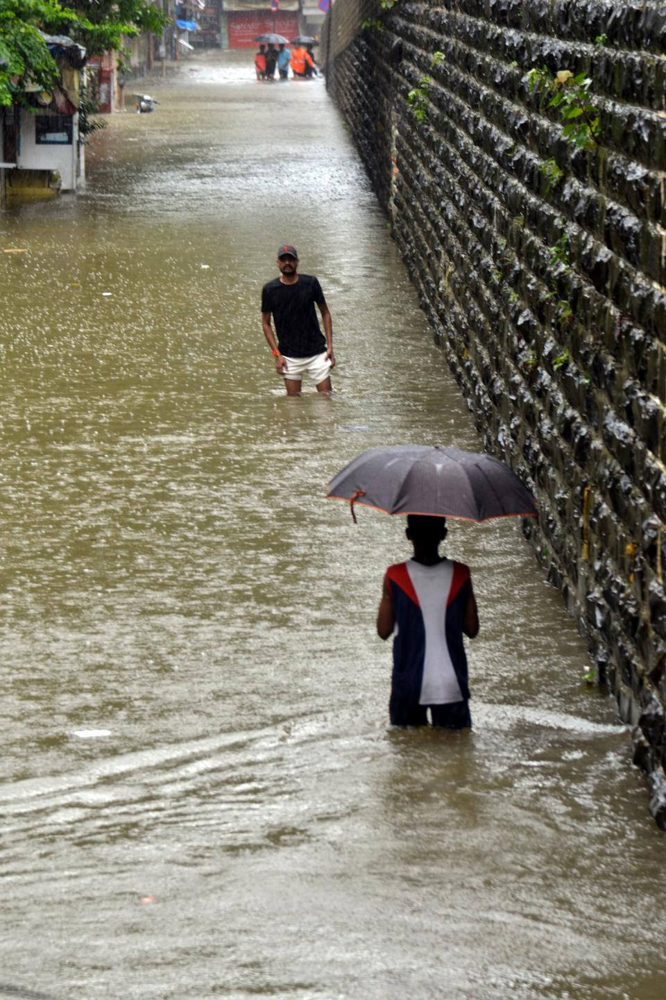 People wade along a flooded road during a heavy monsoon rainfall in Mumbai on August 4, 2020. (Photo by Sujit Jaiswal / AFP) (Photo by SUJIT JAISWAL/AFP via Getty Images)
