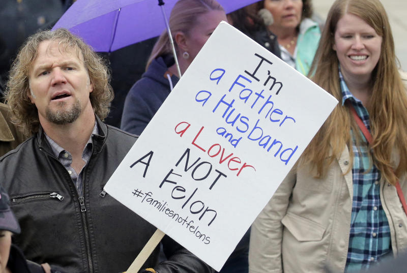"FILE - In this Feb. 10, 2017, file photo, Kody Brown, left, from TV's reality show ""Sister Wives,"" marches during a protest at the state Capitol, in Salt Lake City. Polygamists have lived in Utah since before it became a state, and 85 years after the practice was declared a felony they still number in the thousands. It's even been featured in the long-running reality TV show, ""Sister Wives."" Now, a state lawmaker says it's time to remove the threat of jail time for otherwise law-abiding polygamists. (AP Photo/Rick Bowmer, File)"