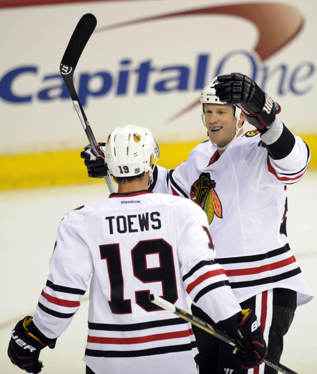 Chicago Blackhawks left wing Brad Winchester, right, celebrates his goal with teammate Jonathan Toews (19) against the Washington Capitals during the second period an NHL preseason hockey game on Friday, Sept. 20, 2013, in Washington. (AP Photo/Nick Wass)