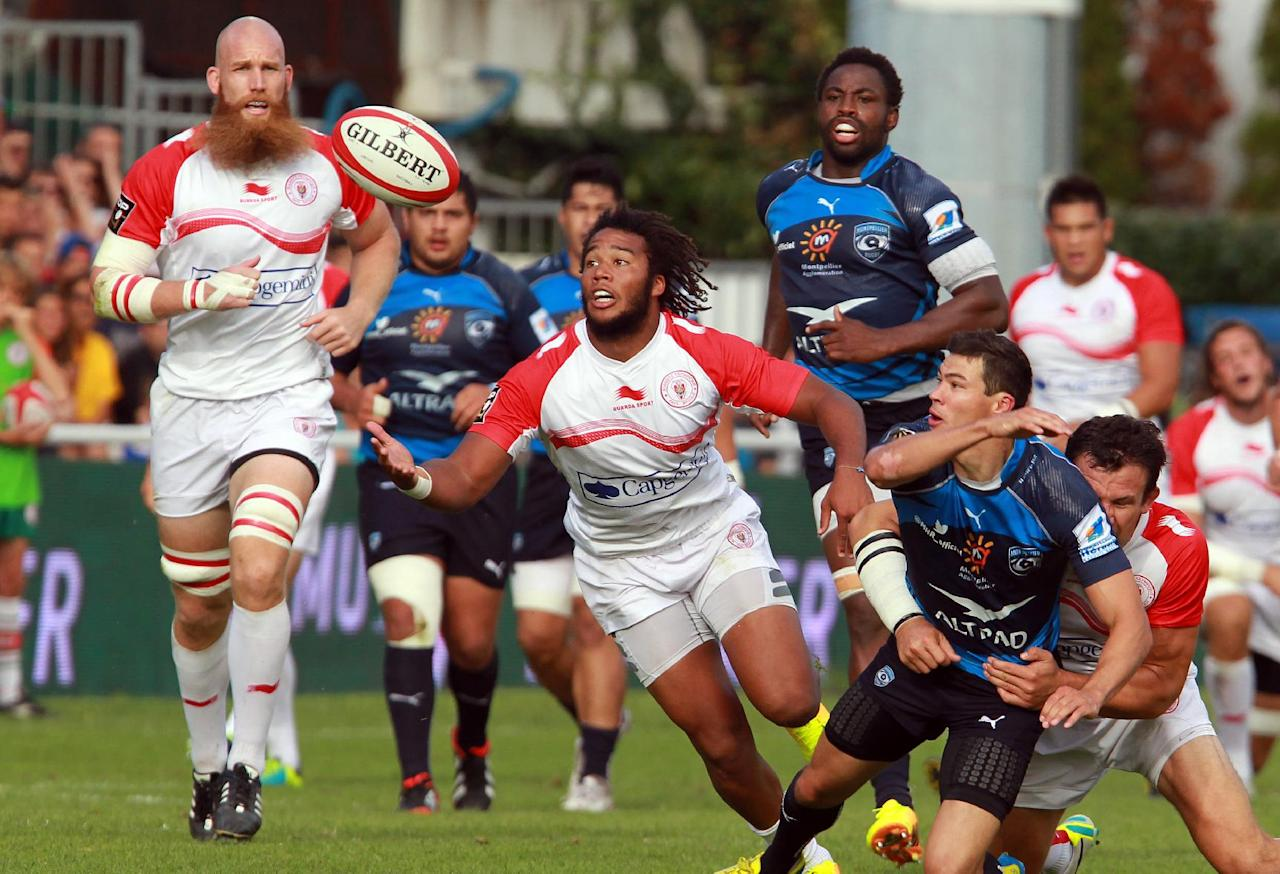 Biarritz's Teddy Thomas, centre, breaks through the challenge of Montpellier's players as Biarritz's Erik Lund, left, looks on during their French Top 14 rugby union match at the Stade Aguilera, in Biarritz, southwestern France, Saturday Aug. 24, 2013. (AP Photo/Bob Edme)