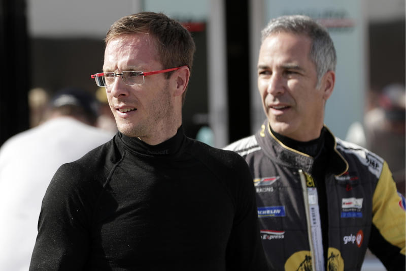 FILE - In this Friday, Jan. 3, 2020, file photo, Sebastien Bourdais, left, and Joao Barbosa walk back to their garage after a practice session during testing for the upcoming Rolex 24 hour auto race at Daytona International Speedway in Daytona Beach, Fla. Bourdais spent a day in early November helping IndyCar fine-tune its newest safety innovation. Later that night, he learned he was likely losing his job with a year remaining on his contract. (AP Photo/John Raoux, File)