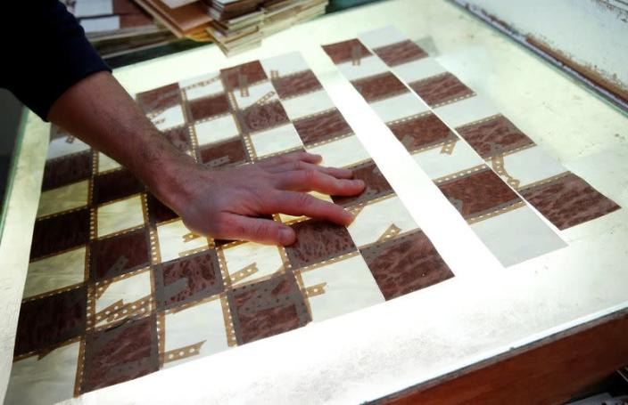 A worker makes a chess board at the Rechapados Ferrer factory at their factory in La Garriga