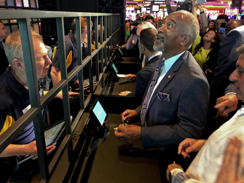 State Assemblyman Gary Pretlow, D-Westchester County, places a bet at Rivers Casino and Resort, Tuesday, July 16, 2019, in Schenectady, N.Y. New York joined the growing list of states allowing wagering on sports after the upstate casino cut the ribbon on a new betting lounge Tuesday and took its first bet — $20 on the Seattle Mariners. (AP Photo/David Klepper)