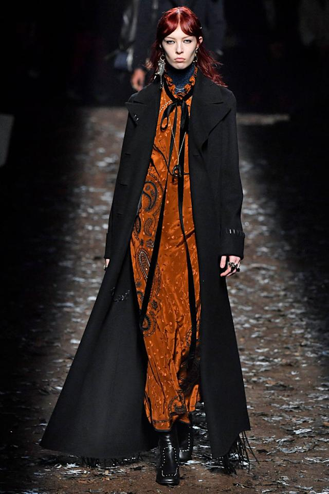<p>A model wears an orange bandana-print maxi dress with long black coat at the Coach Fall 2018 show. (Photo: Getty) </p>