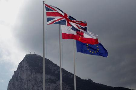 Union Jack, the Gibraltarian flag and the EU flag are seen flying, at the border of Gibraltar with Spain
