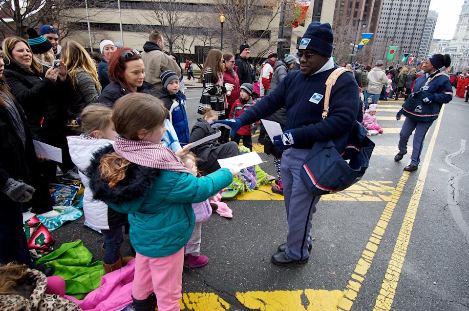 Philadelphia, PA, USA - November 27, 2014: Letter Carriers with the USPS are seen collecting mail addressed to Santa Claus during the Thanksgiving Day Parade in Philadelphia.