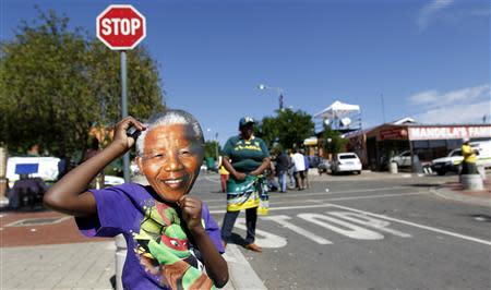 A boy wears a mask of former South African President Mandela outside his house along Vilakazi Street in Soweto, where Mandela resided when he lived in the township