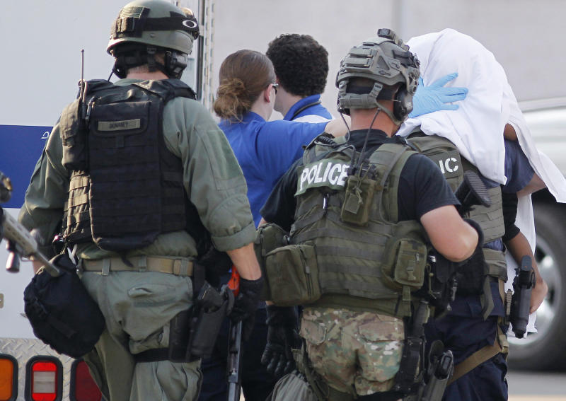 In this Thursday, Aug. 23, 2012 photo, authorities remove a child from the house in Washington Park, Ill., where a teenage girl told police she escaped earlier this week with a relative's help. The teen says she was held captive and sexually assaulted every day for two years. She said the child is the result of rape by her captor. (AP Photo/Belleville News-Democrat, Zia Nizami)
